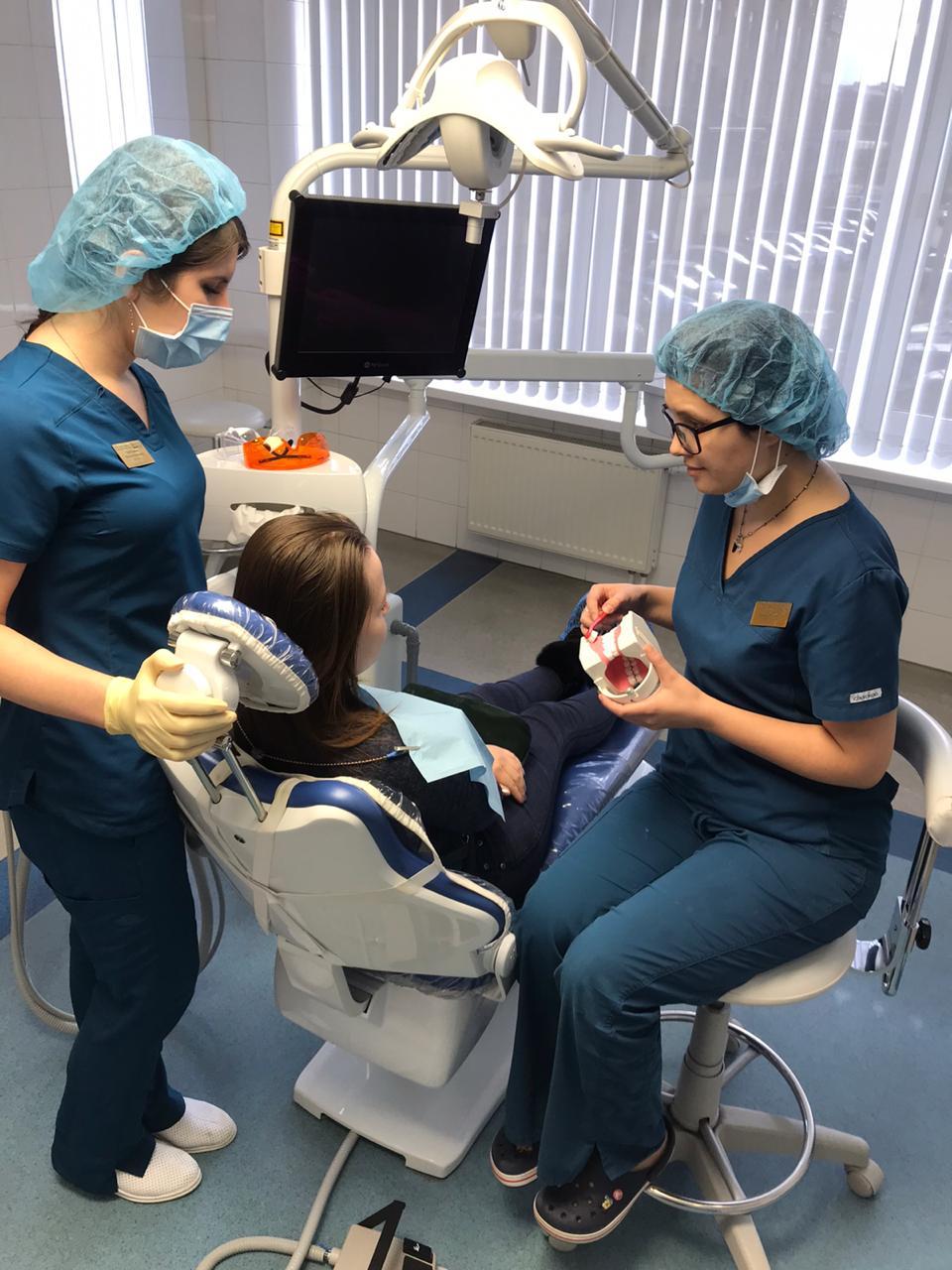 Пациент в кресле окло него врач и асссистент
